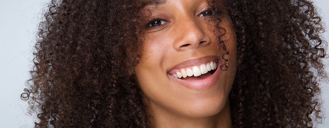 happy-african-american-woman-with-curly-hair-PR47SHE